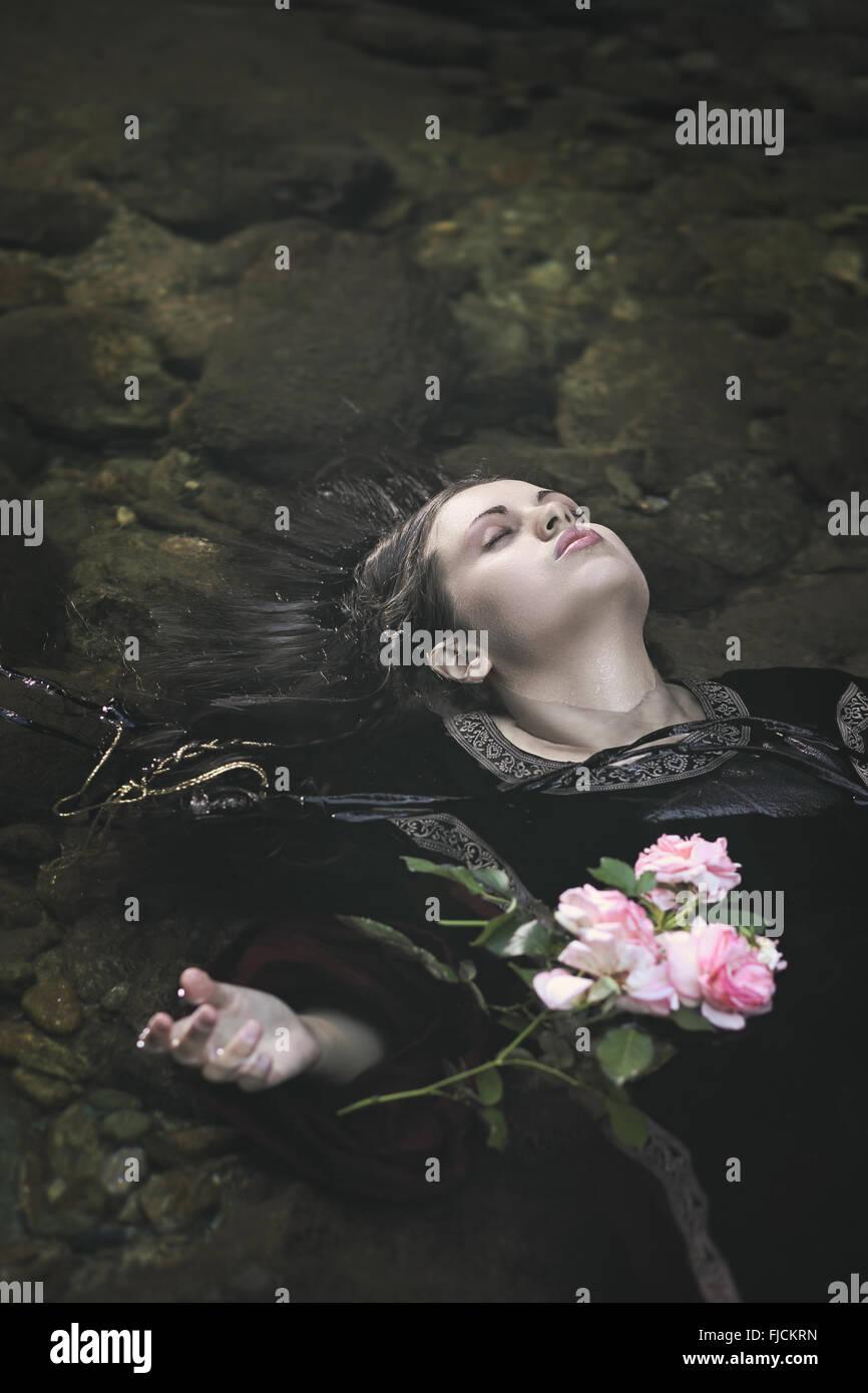 Schöne Frau in einem Fluss zu ertränken. Ophelia-Konzept Stockbild