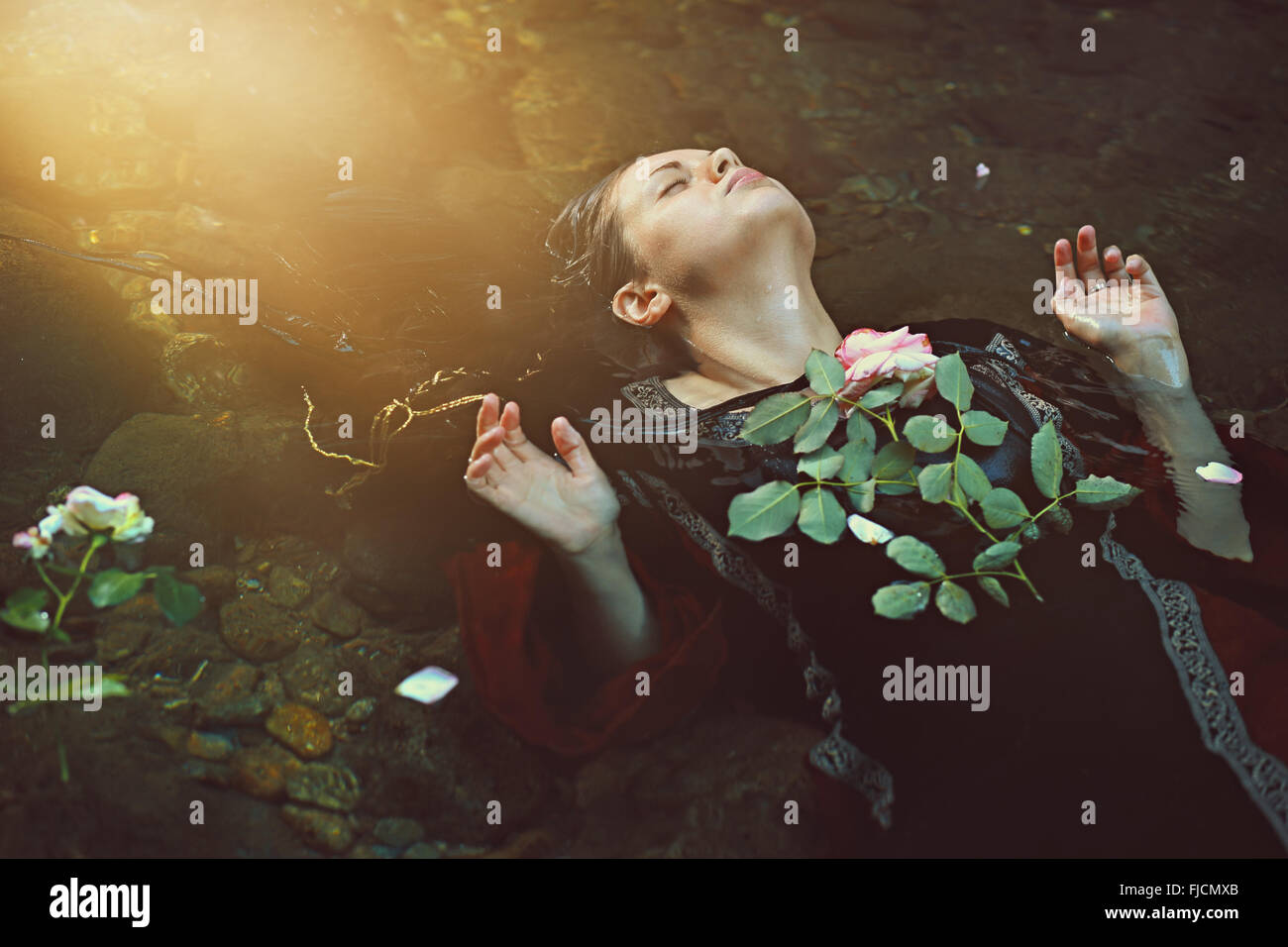 Frau im dunklen Wasser-Strom und weiche Sonnenlicht. Romantik und Tragik Stockbild