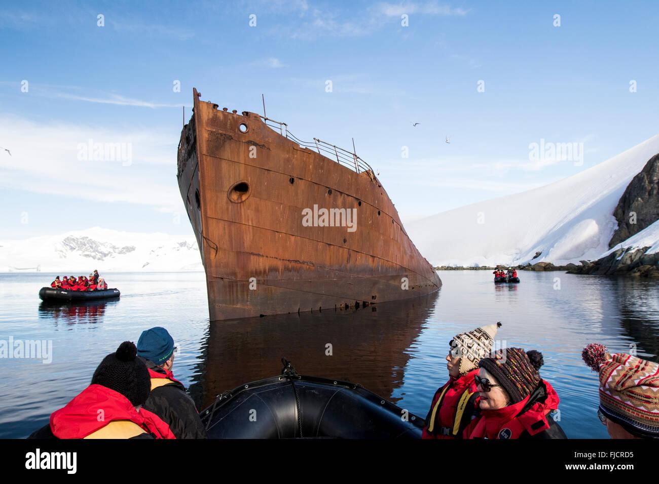 Antarktis Tourismus mit Kreuzfahrtschiff Passagiere in Zodiac Boot Anzeigen von alten und historischen Walfangschiff. Stockbild