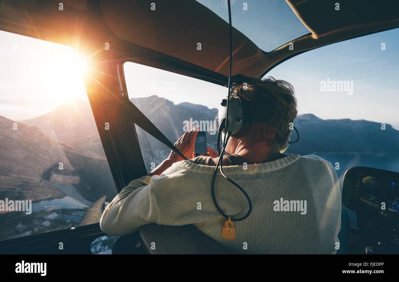Heckansicht des weiblichen Touristen auf Hubschraubertour fotografieren während des Fluges über Berge Stockbild