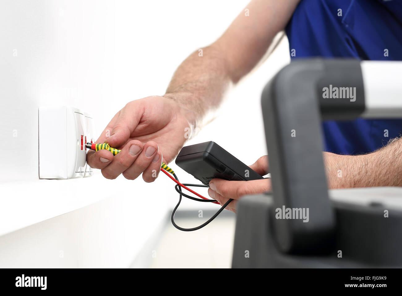 Elektriker. Installation von Internet. Installation von der Steckdose. Man steigt in eine elektrische Steckdose, Stockfoto