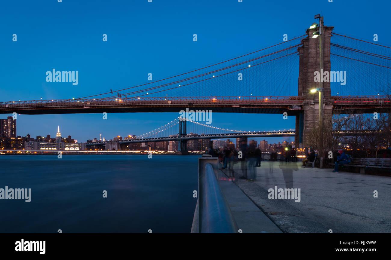Blick auf die Brooklyn Bridge und Manhattan Bridge in der Dämmerung an der Promenade im Brooklyn Bridge Park Stockbild