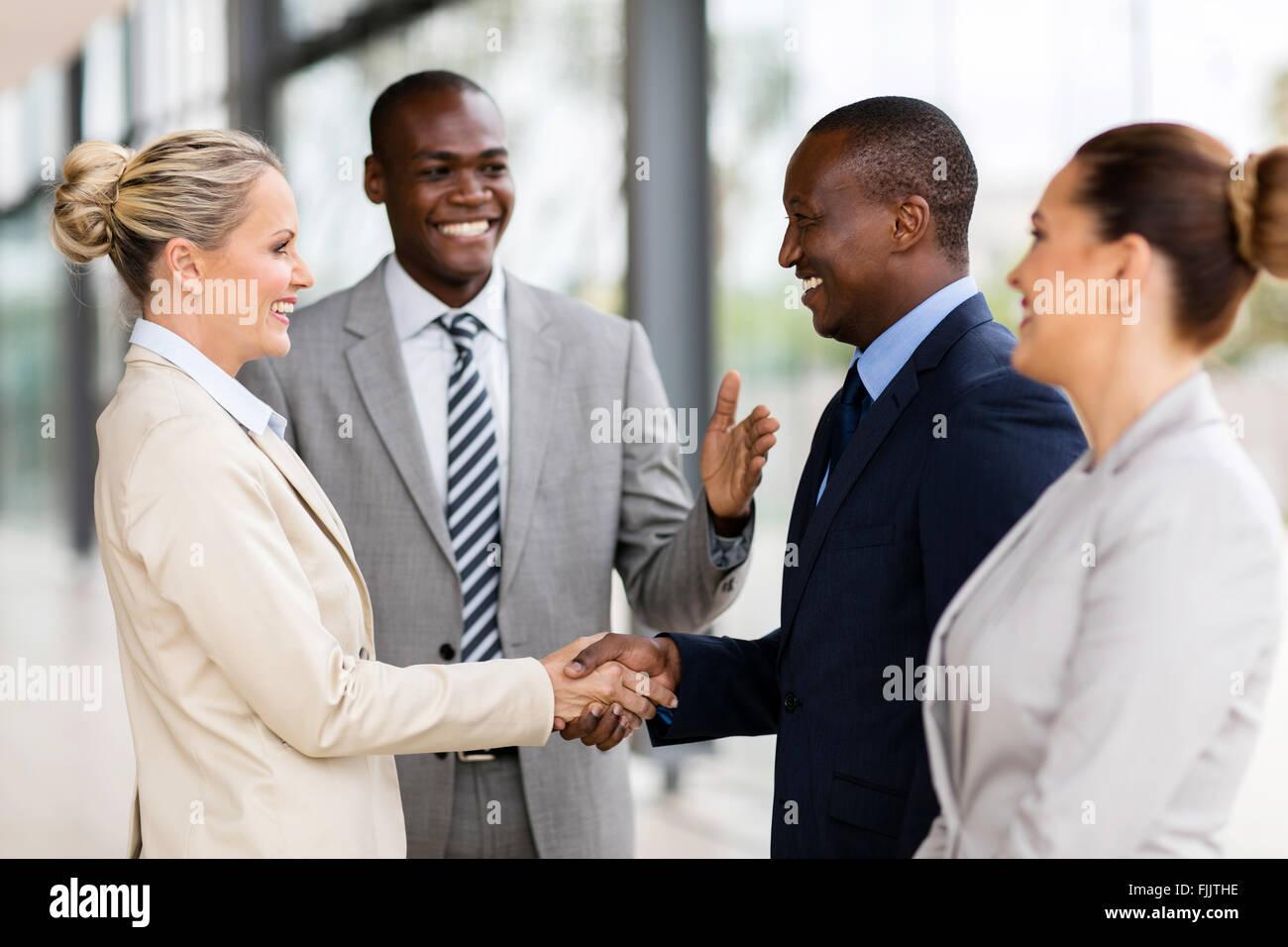 glücklich afrikanischen Mann Einführung Geschäftsfrau an Geschäftspartner Stockbild