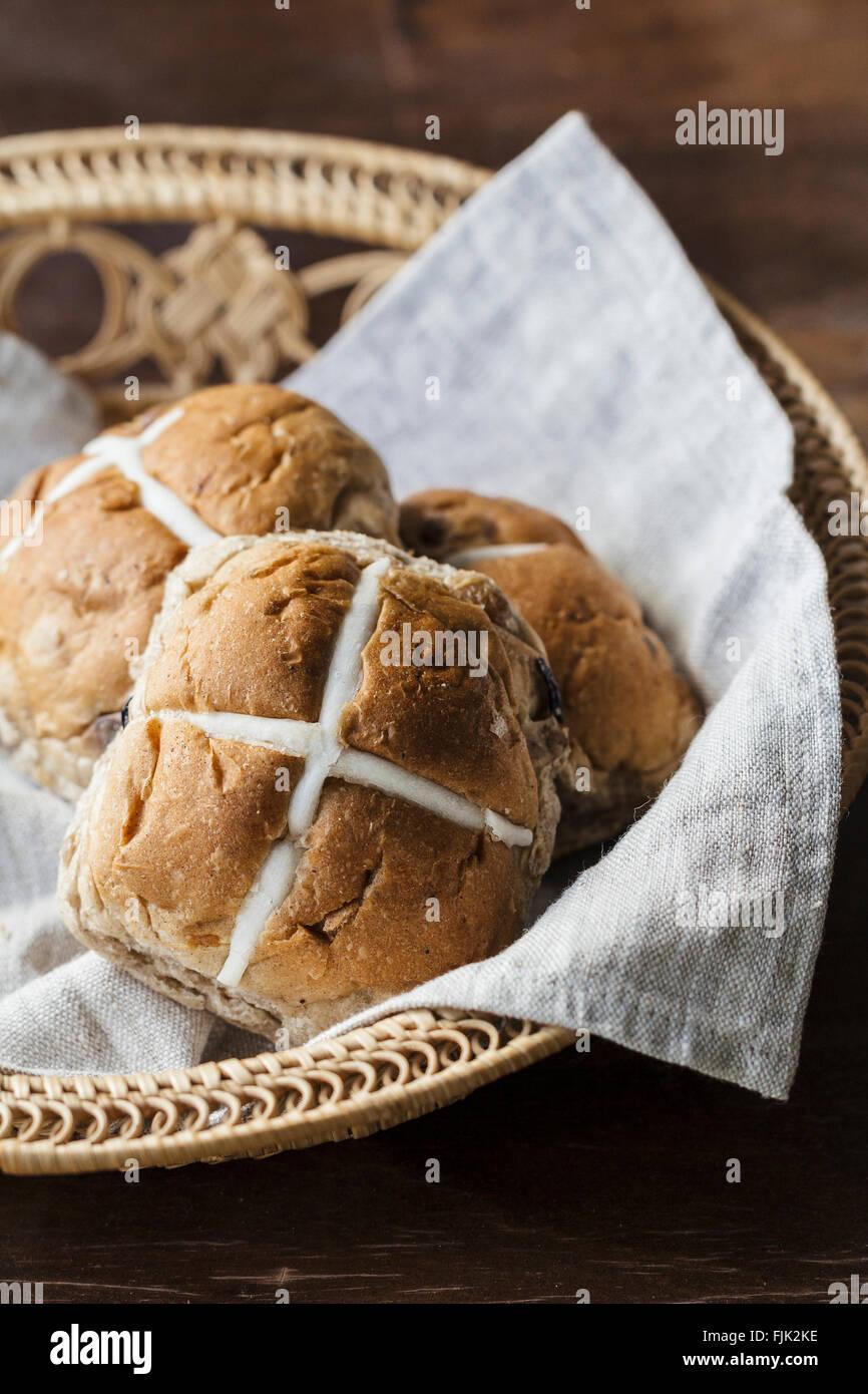 Drei Ostern Hot Cross Buns in einem Korb auf einem rustikalen Holztisch Stockbild