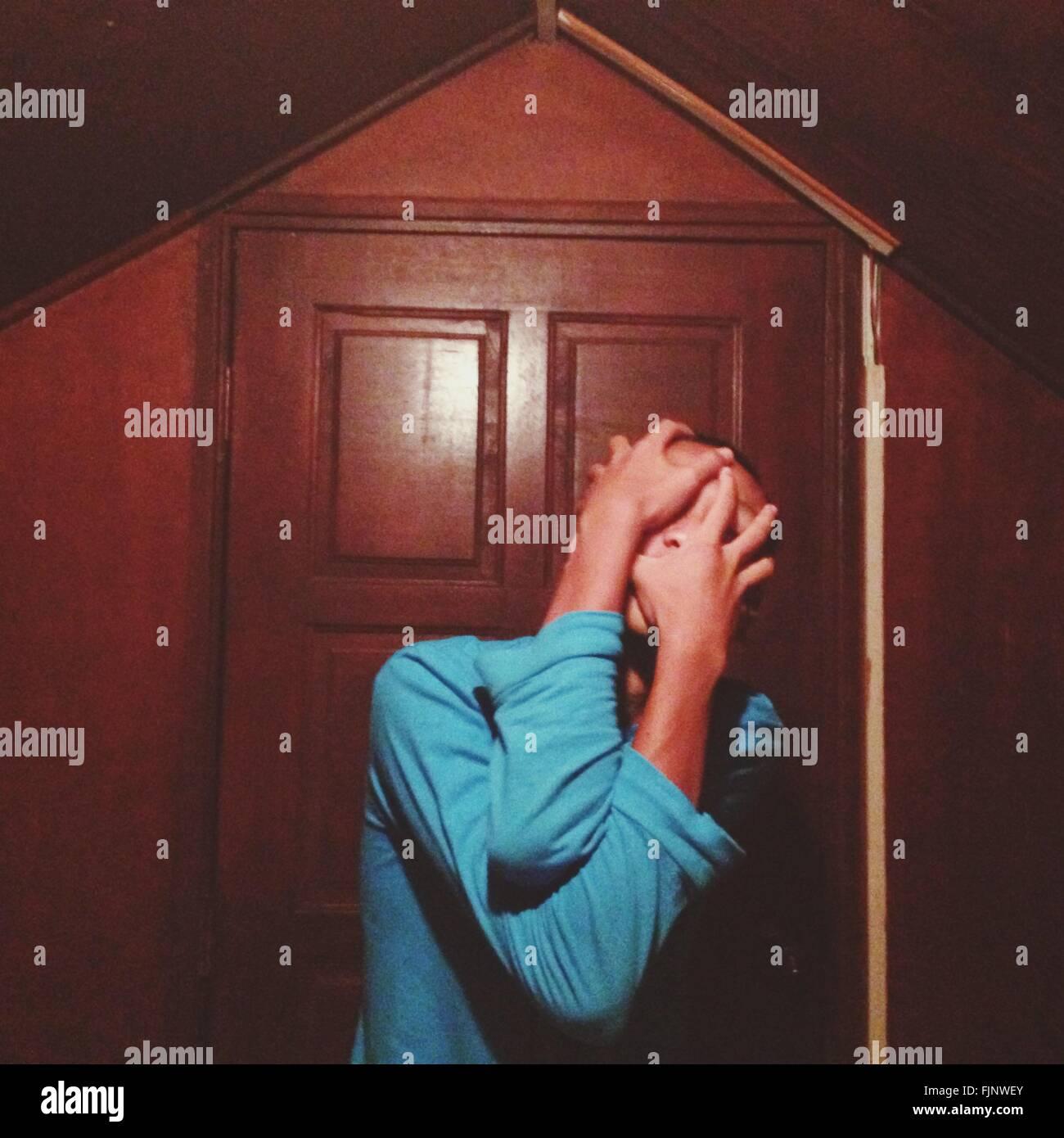 Manndeckung Gesicht mit Händen vor Haus Stockfoto