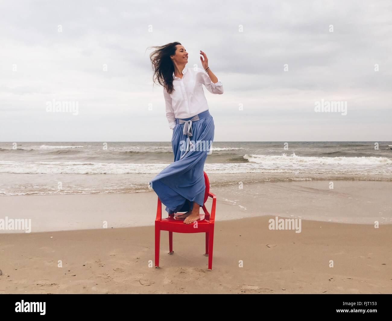Schöne Frau auf Stuhl am Strand gegen bewölktem Himmel Stockbild