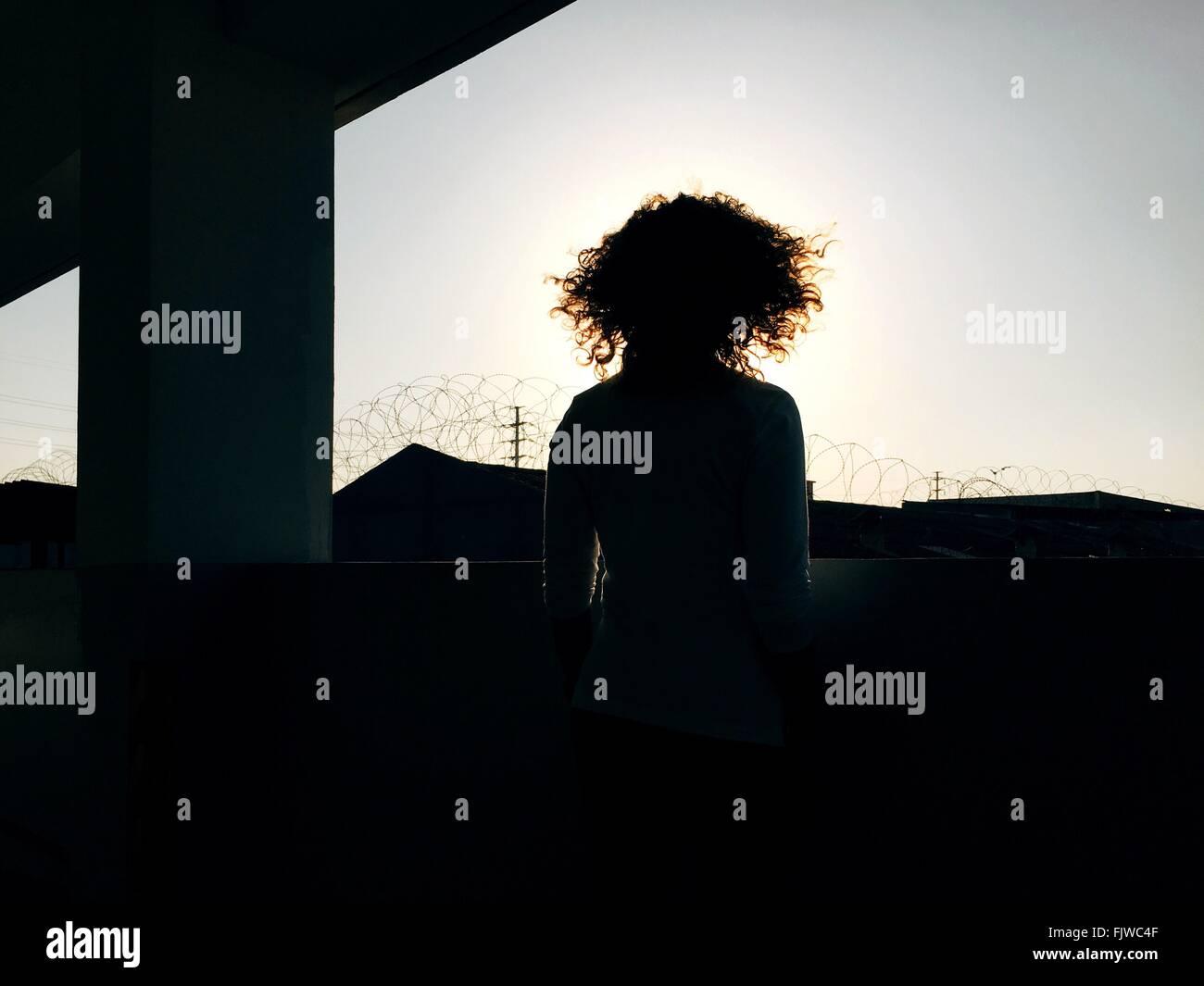 Hintere Ansicht Frau mit lockigem Haar unten Brücke gegen Himmel stehen Stockbild