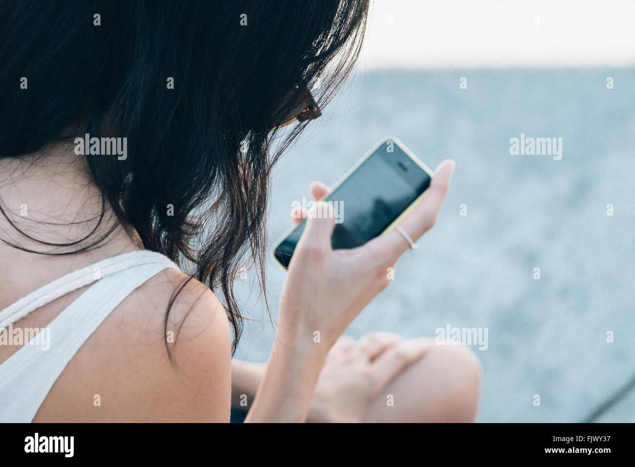Rückansicht des Frau mit Smartphone Stockbild