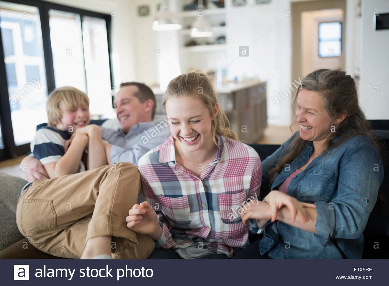 Lachend Familie auf Sofa im Wohnzimmer Stockbild