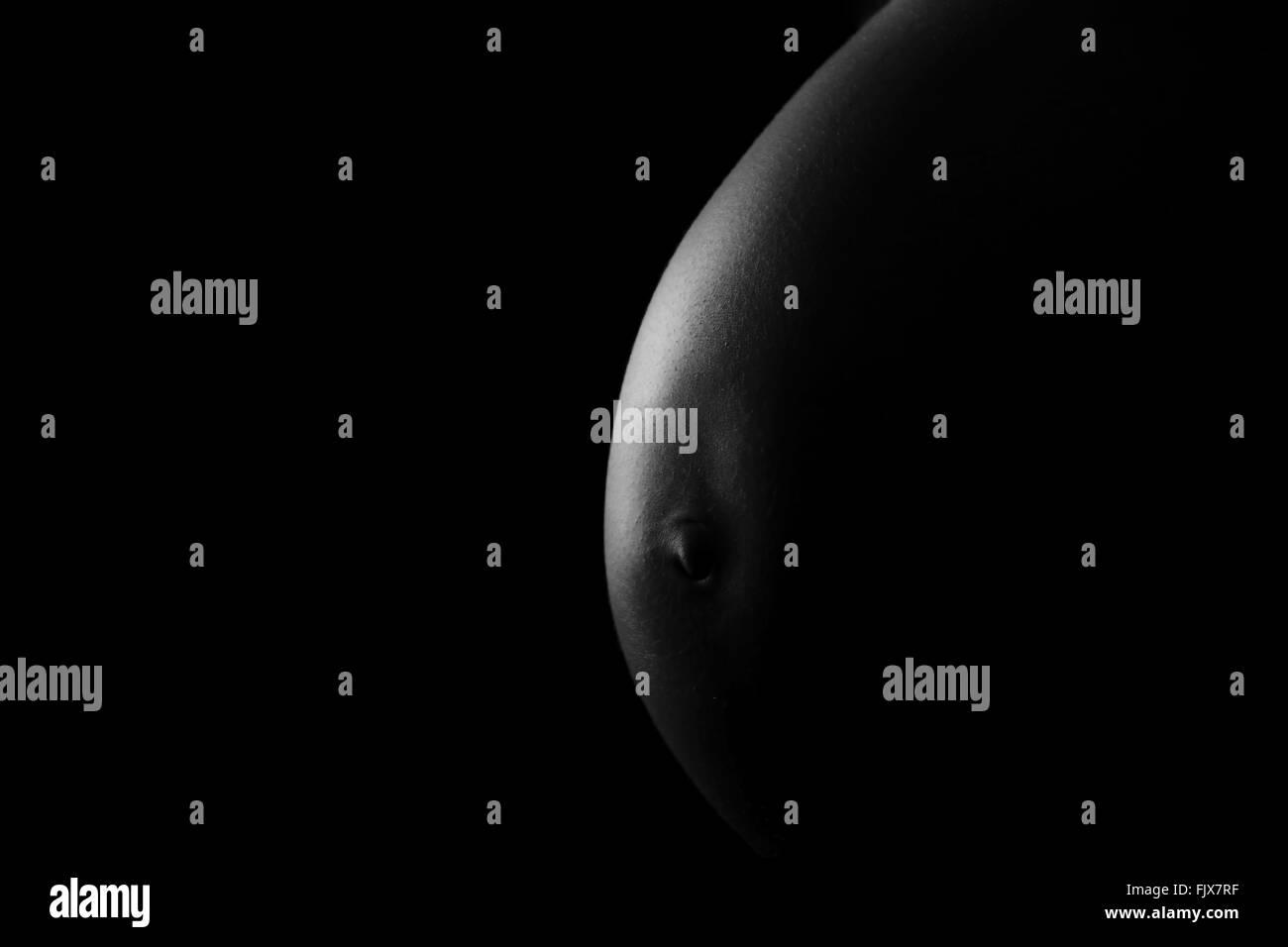 Mittelteil der schwangeren Frau auf schwarzem Hintergrund Stockbild