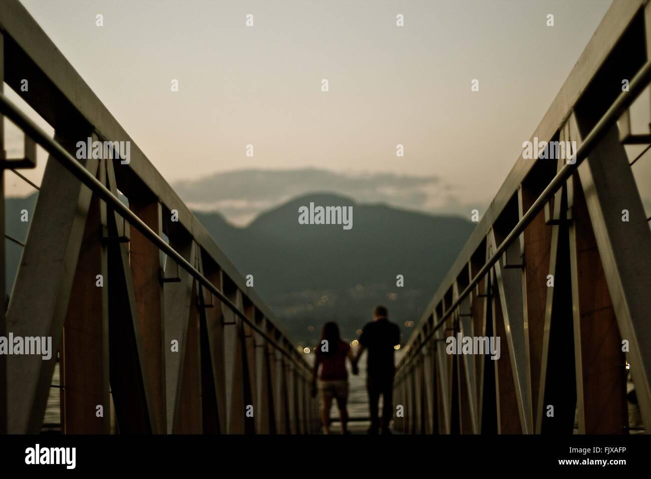 Rückansicht des Paares Geländer entlang Stockbild