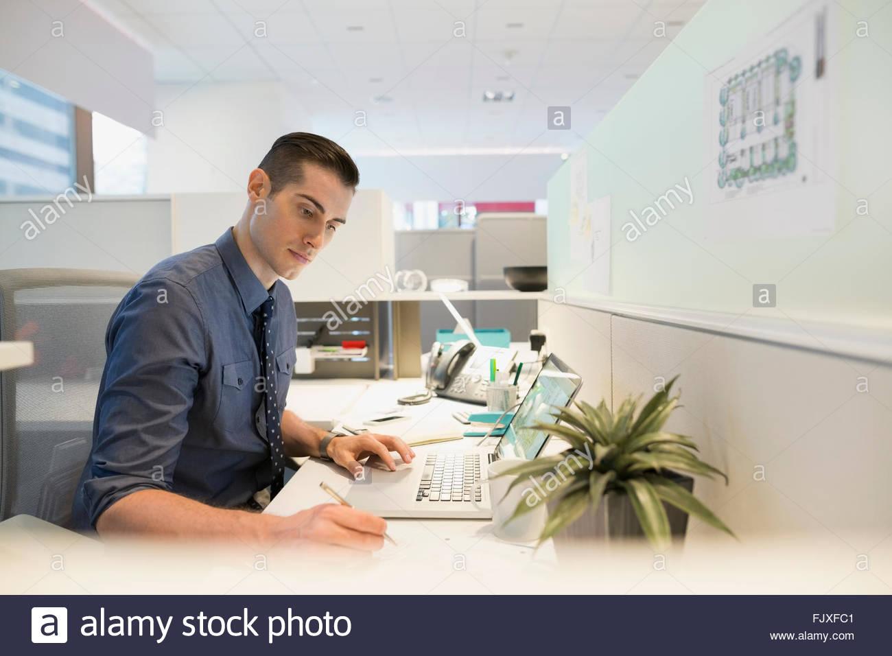 Fokussierte Geschäftsmann mit Laptop am Schreibtisch Stockbild