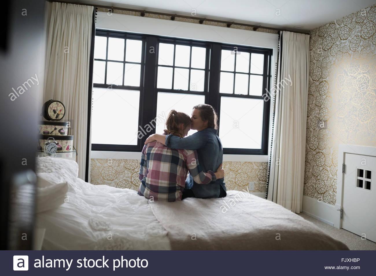 Mutter zu umarmen und küssen Teenager-Tochter im Schlafzimmer Stockbild