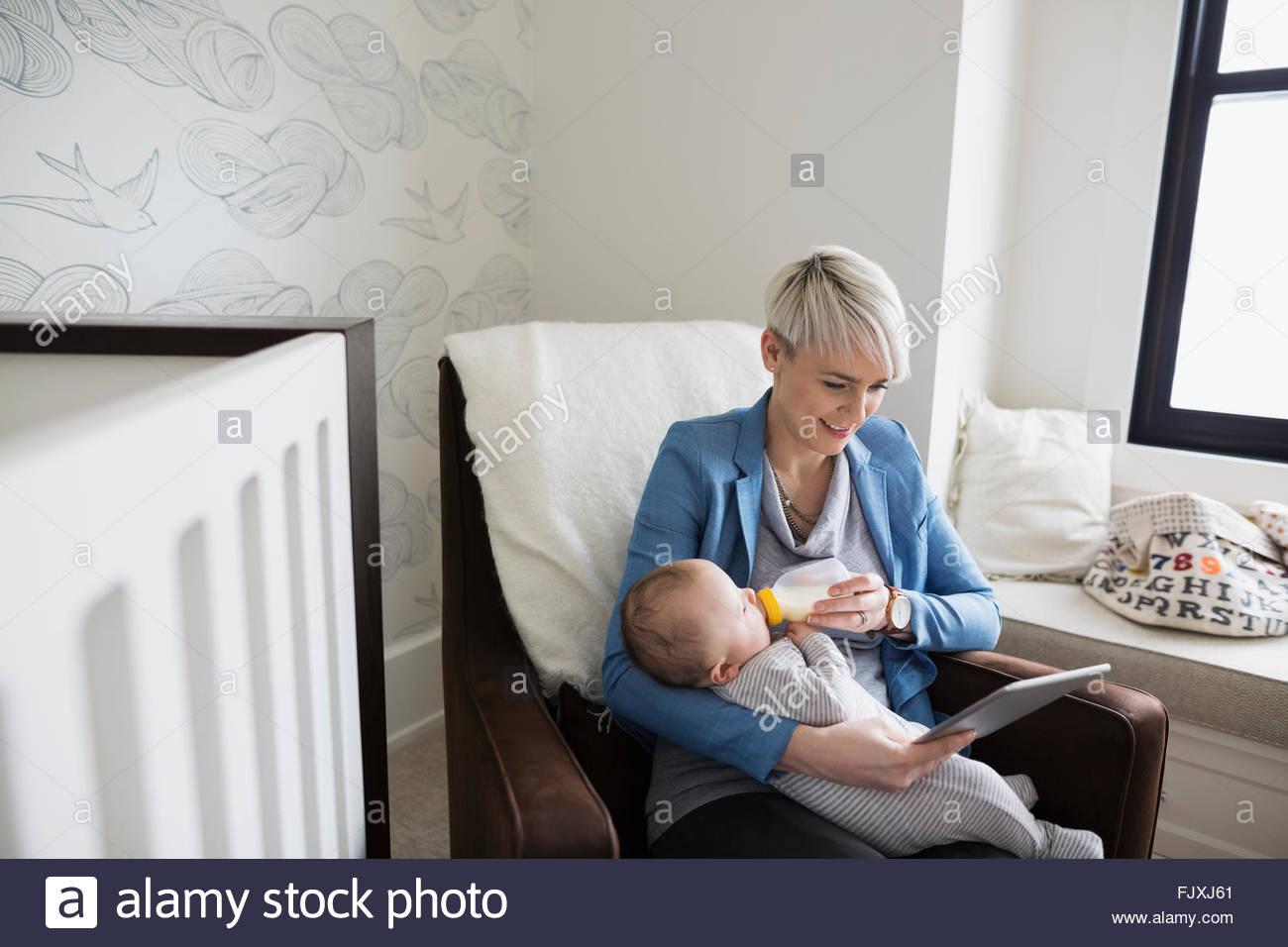 Mutter mit digital-Tablette Fütterung Sohn Babyflasche Stockbild