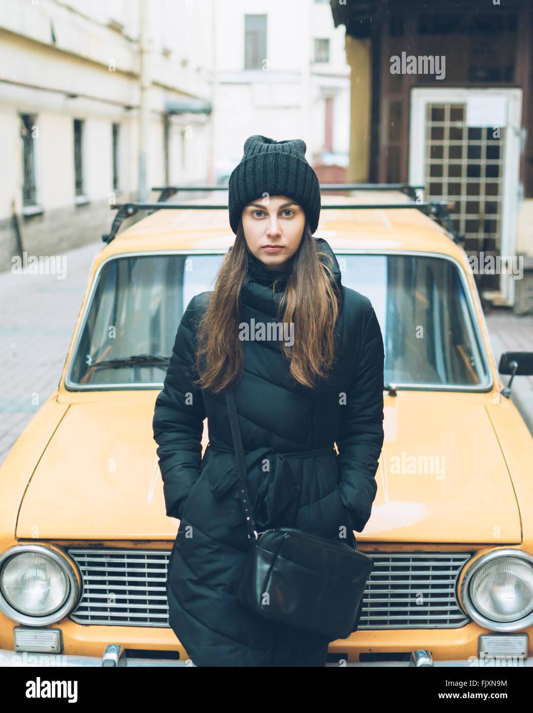 Porträt der schönen jungen Frau stützte sich auf Straße geparkten Auto Stockbild