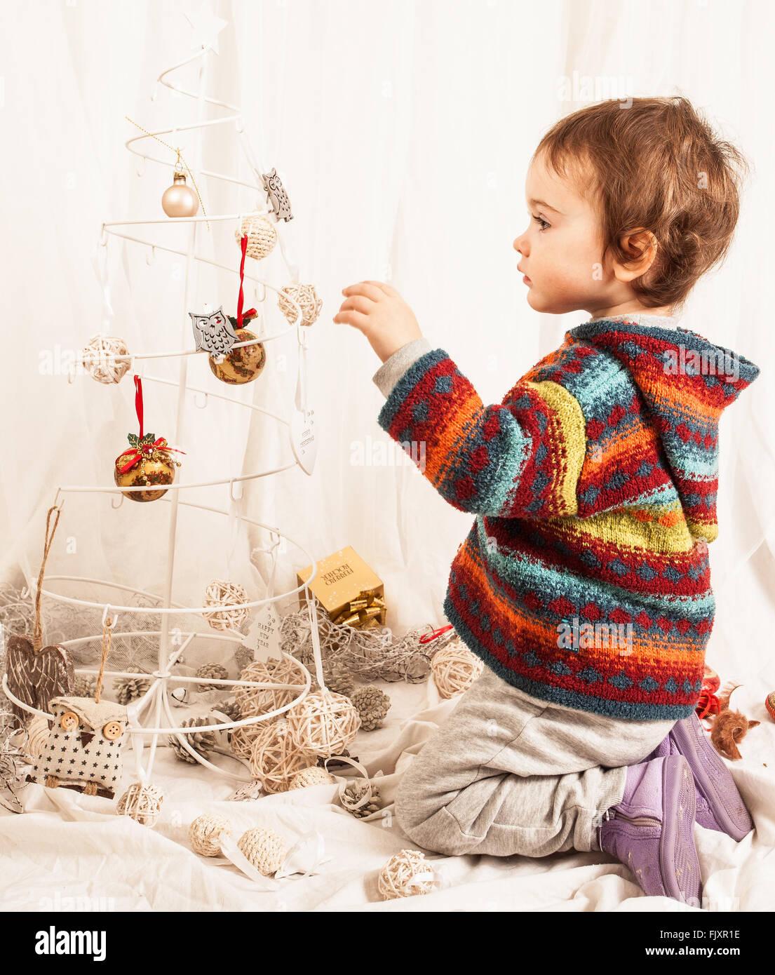 Jungen spielen mit Weihnachtsdekoration auf Bett zu Hause Stockbild