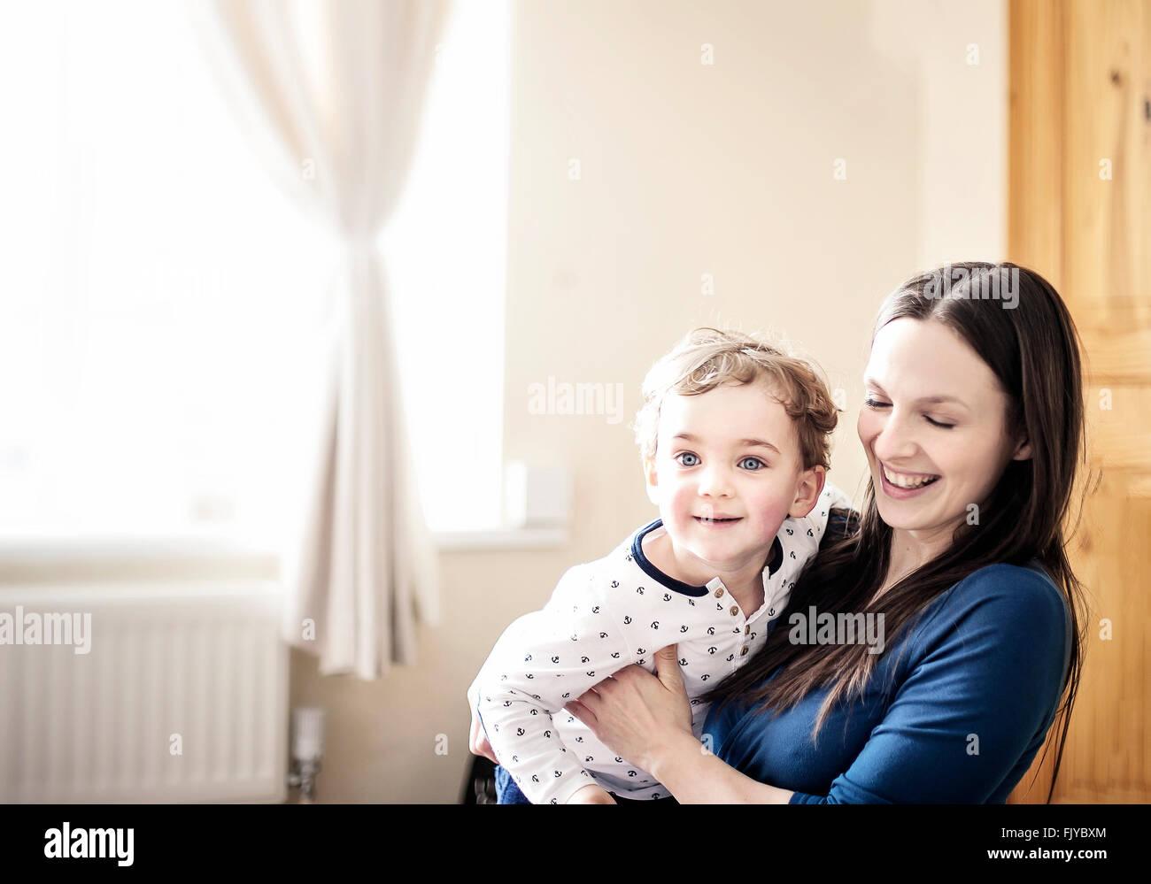 junge Mutter mit ihrem kleinen Jungen im Zimmer spielen Stockbild