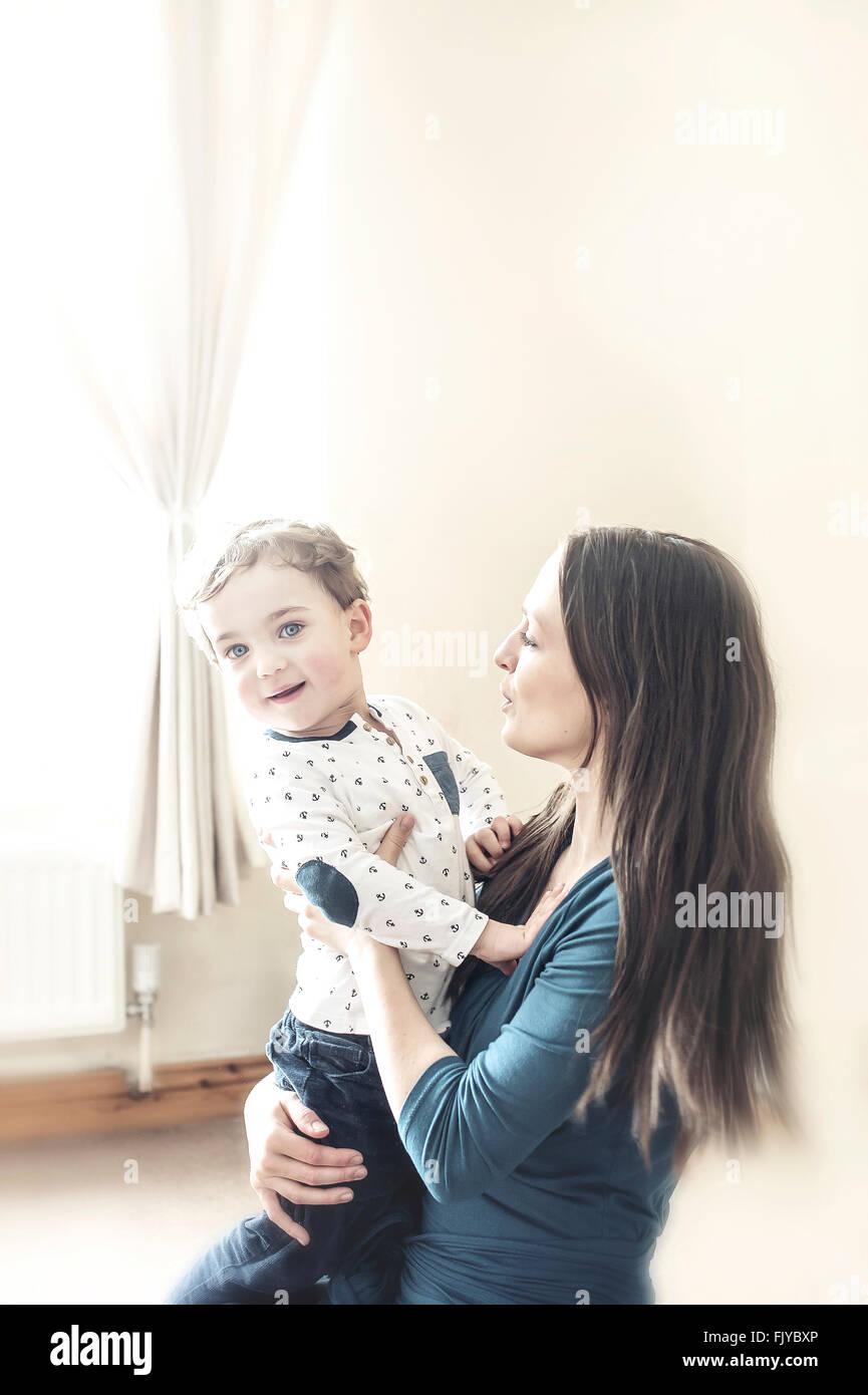 junge Mutter mit einem kleinen Jungen in ihren Armen zu Hause Stockbild