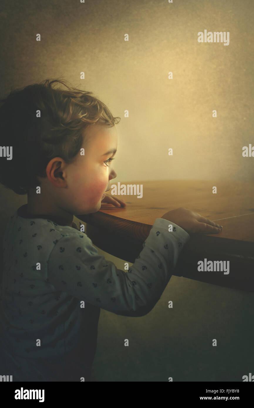 kleiner Junge ruht seine Arme auf dem Holztisch Stockbild