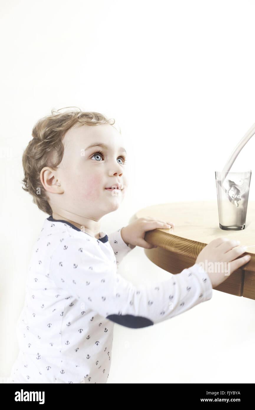 kleiner Junge durch den Holztisch mit Glas Milch Stockbild