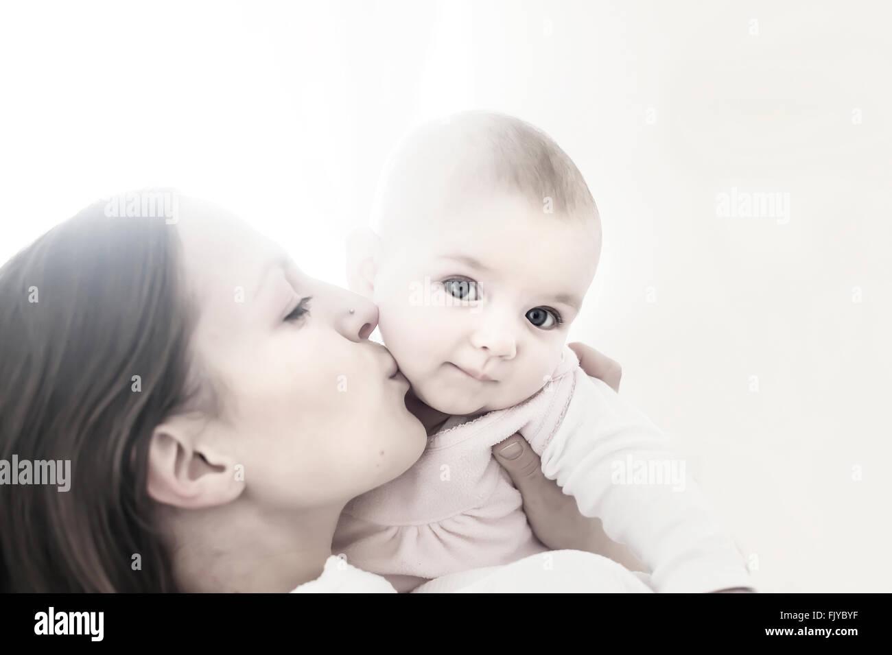junge Mutter küssen ihr Babymädchen in armen Stockbild