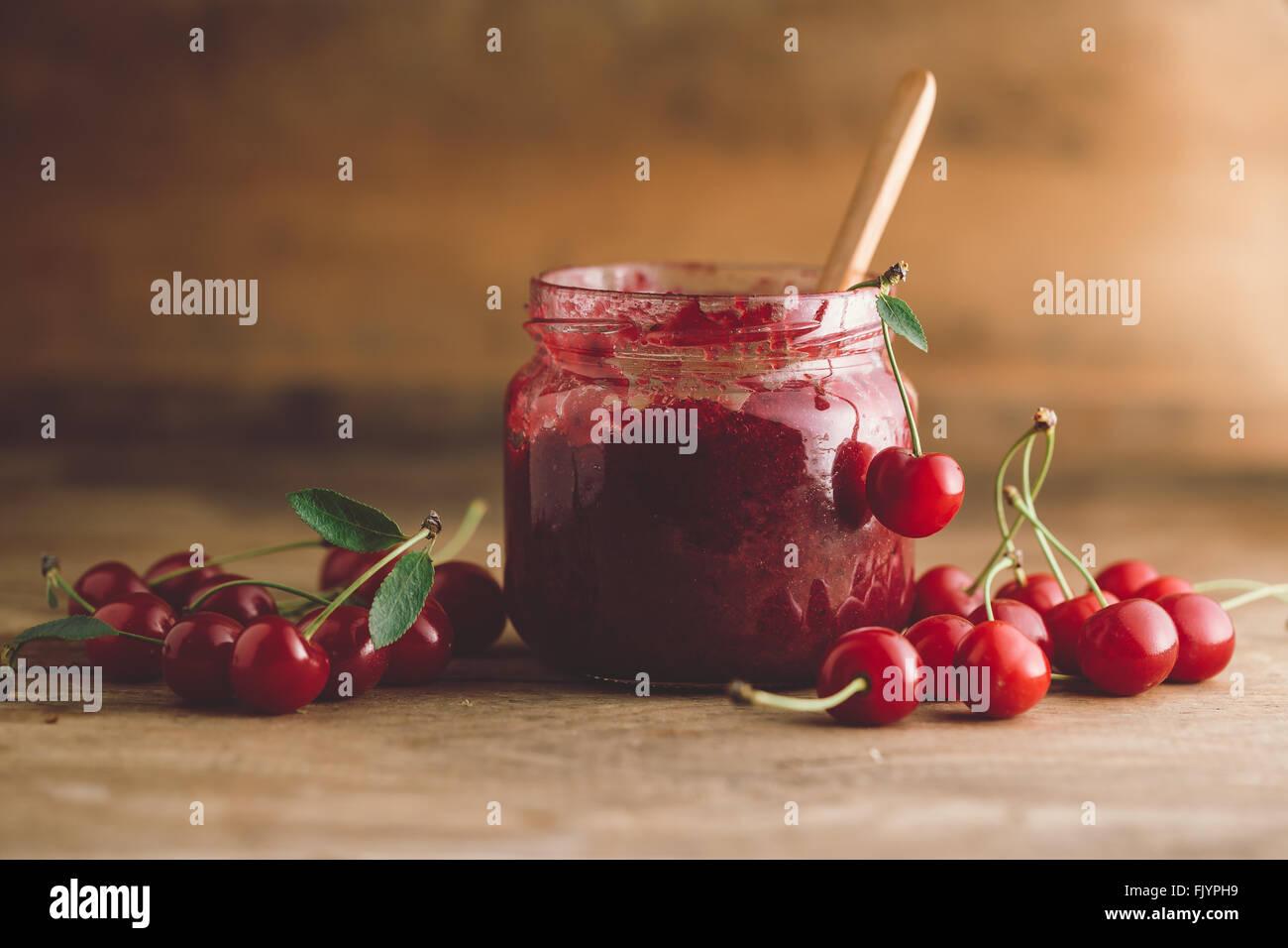 Glas Kirschmarmelade, Sauerkirschen und Löffel Stockbild