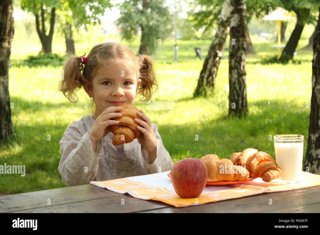 junge Mädchen essen croissant Stockbild