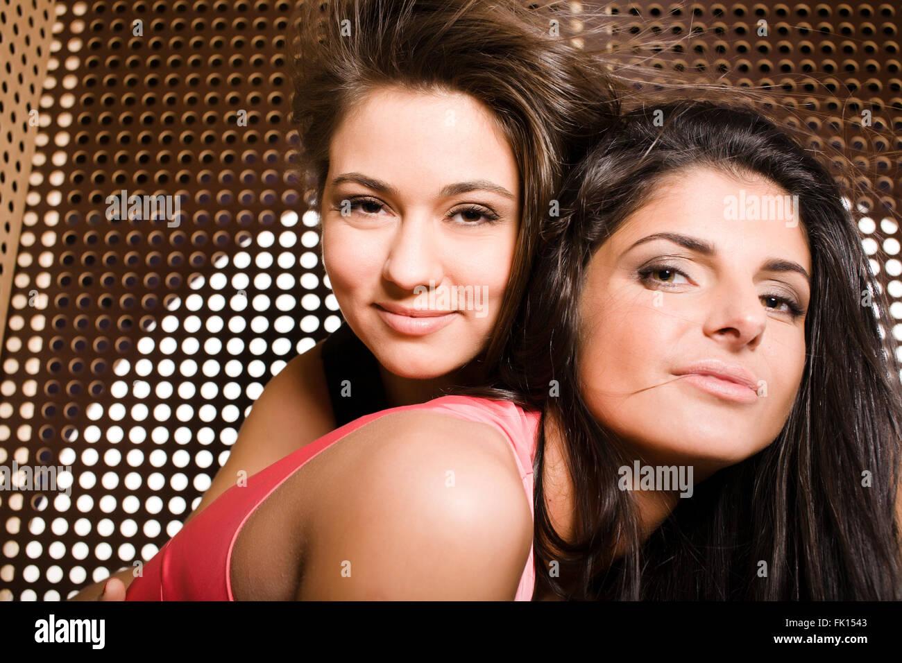 zwei hübsche Freundinnen im Party tanzen schließen sich lächelnd ...