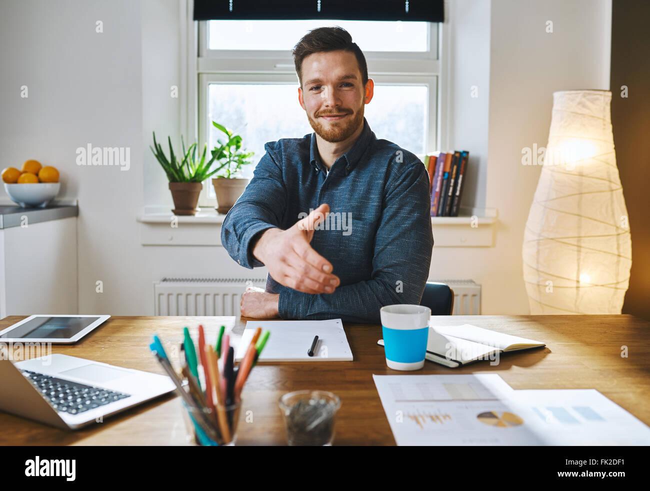 Lächelnd Geschäftsmann lehnt sich auf seinem Schreibtisch bietet seine Hand in Gruß, ein Geschäft in Partnerschaft oder Herzlichen Glückwunsch schließen Stockfoto