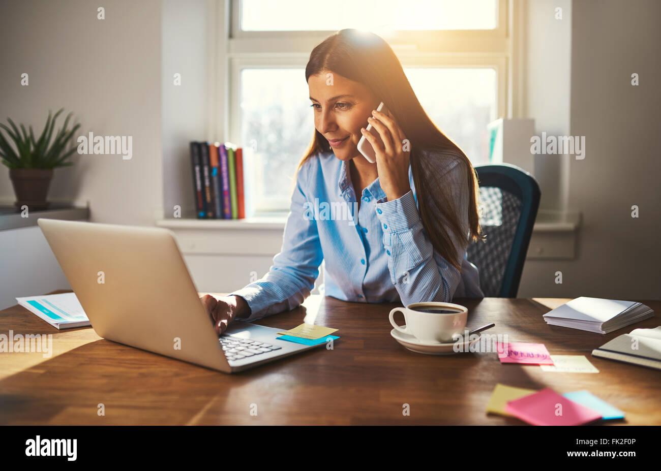 Frau arbeitet am Laptop im Büro während des Gesprächs am Telefon, warmes Licht hinterleuchtet Stockbild