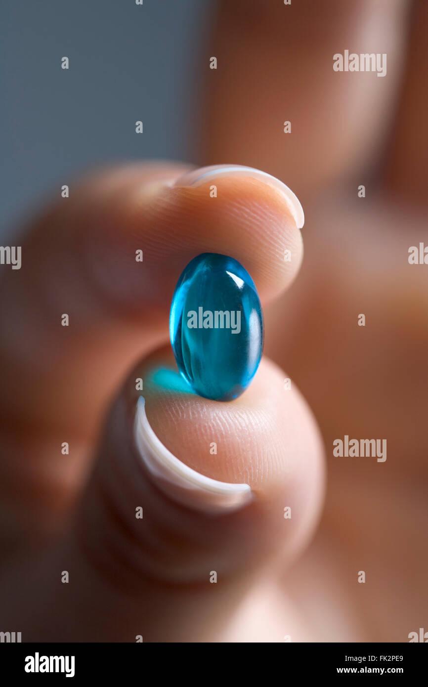 Nahaufnahme von Finger halten eine blaue Kapsel Stockbild