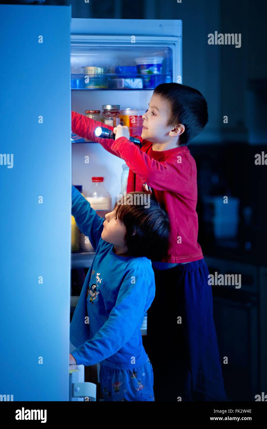 Zwei kleine Jungs, heimlich essen Süßigkeiten aus dem Kühlschrank ...