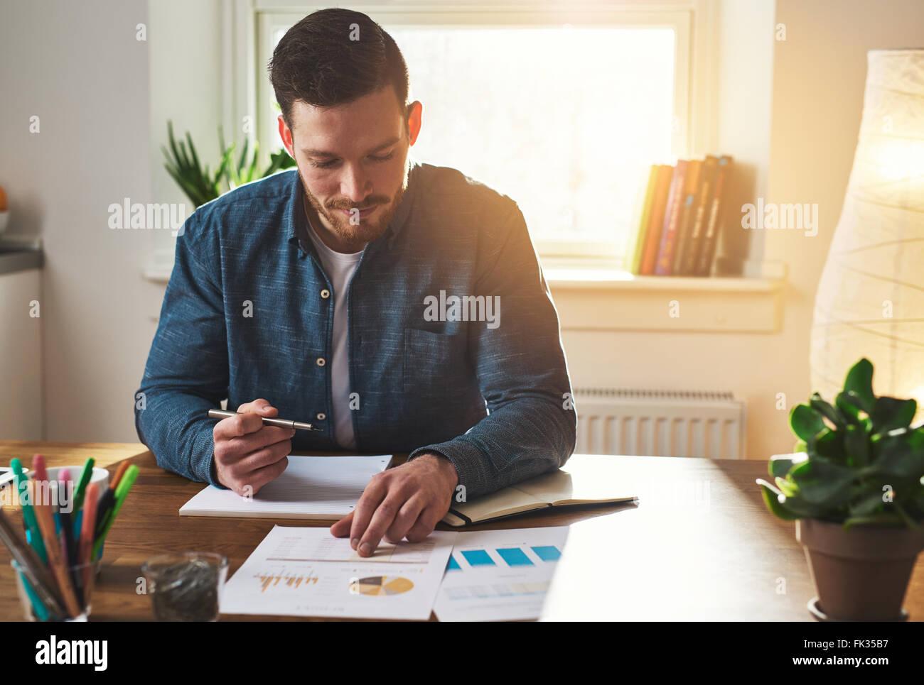 Unternehmer Arbeiten an Business Diagramme und Grafiken wie er Studien, die Leistung seines Small Business und Pläne Stockbild
