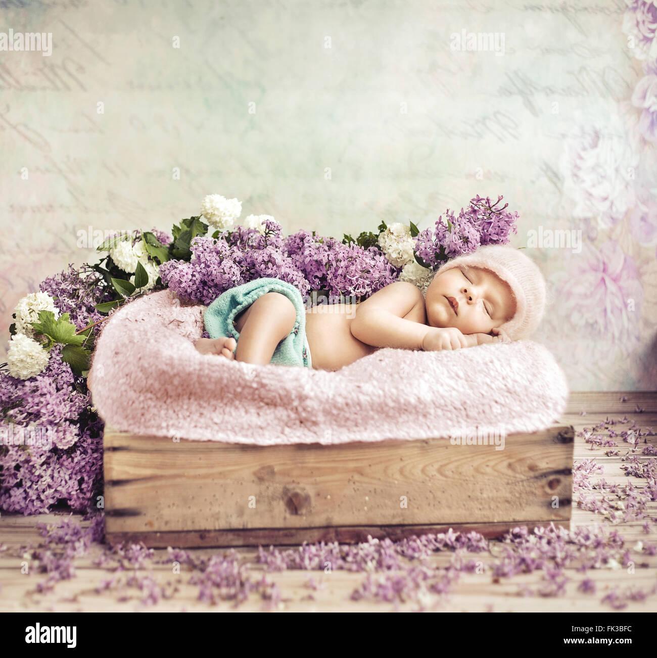 Kleinkind auf lila Blüten und Decke liegend schlafen Stockbild