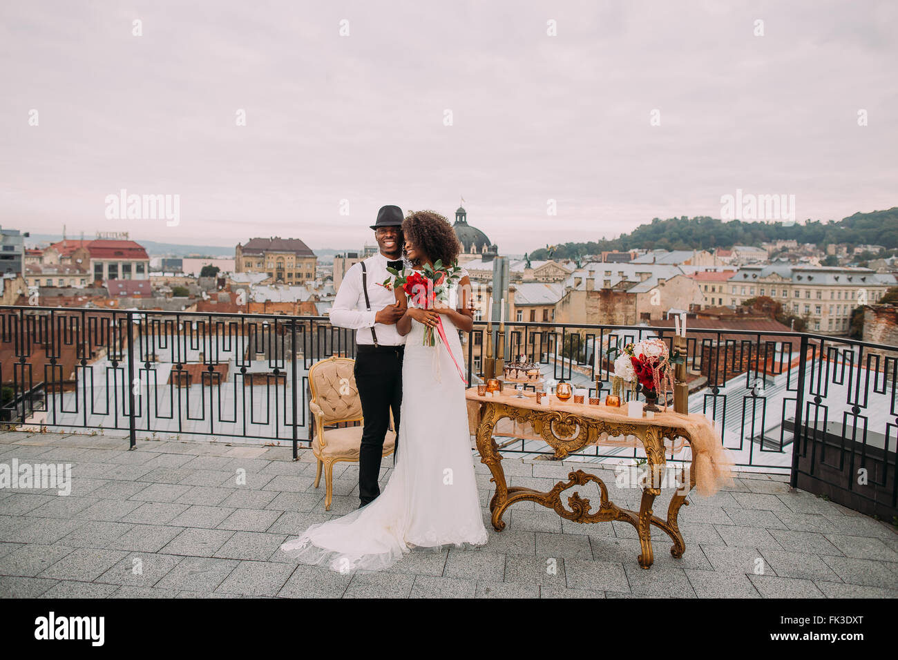 Glücklich afrikanische Braut und Bräutigam glücklich umarmt, auf der Terrasse Stockbild