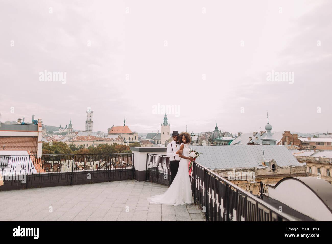 Afrikanische Hochzeitspaar auf dem Dach. Erstaunliche europäischen Lemberg Architektur auf Hintergrund Stockbild