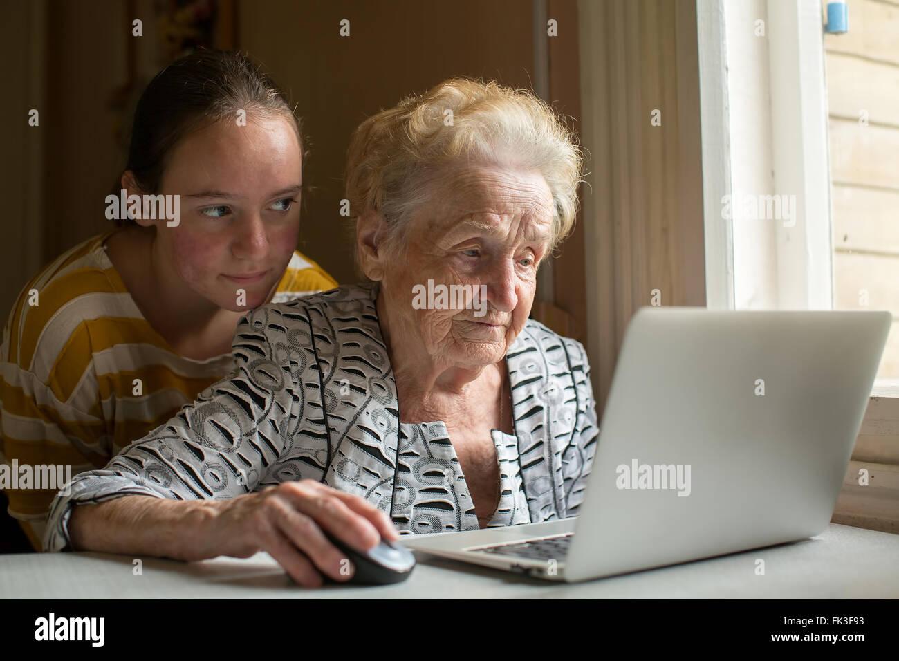 Enkelin lehrt ihre Großmutter auf dem Laptop eingeben. Stockbild