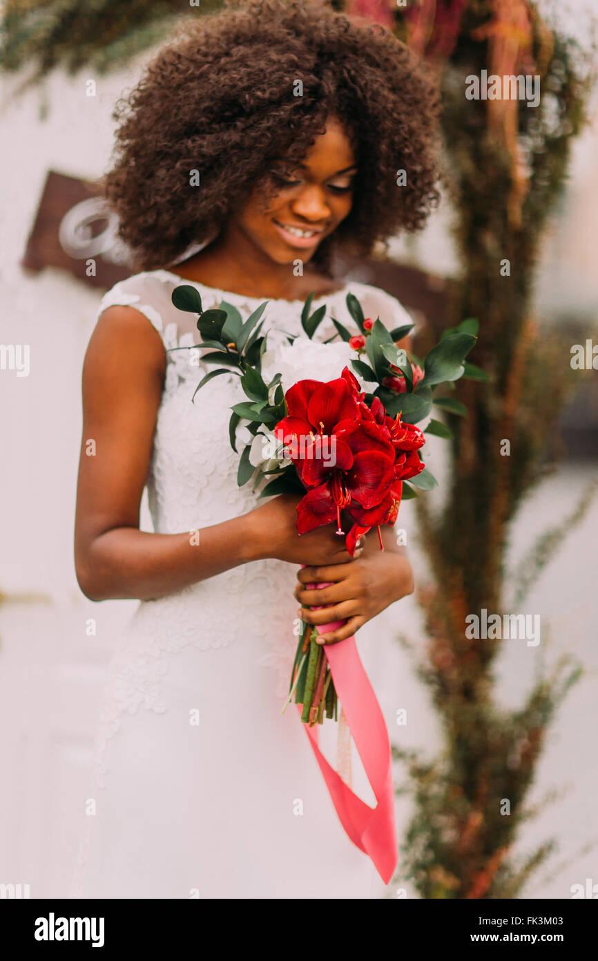 Schöne afrikanische Braut glücklich lächelnd mit roter Blumenstrauß in Händen Stockbild