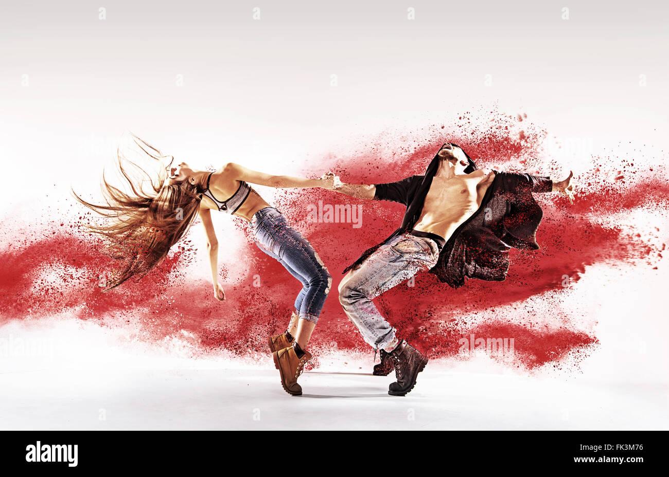 Talentierte junge Tänzerinnen und Tänzer, die roten Sand streuen Stockbild