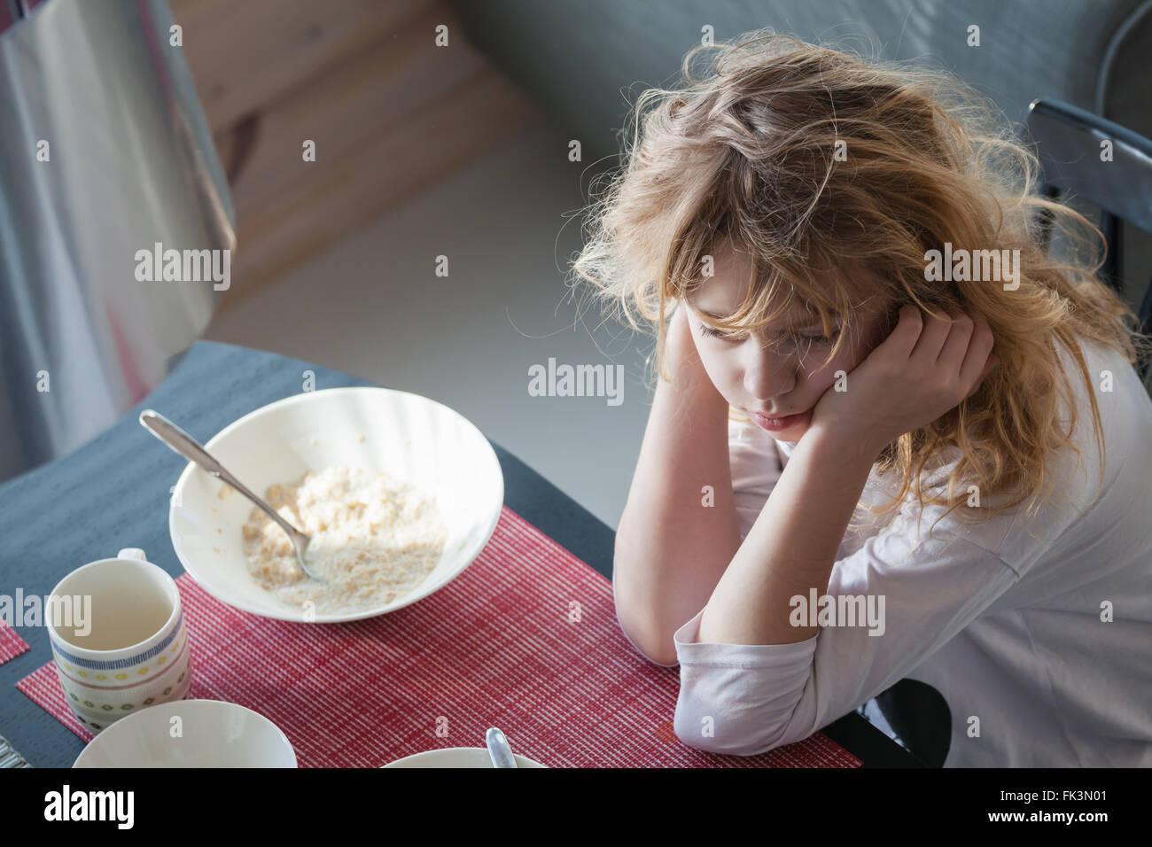 Kleine blonde kaukasische verschlafenes Mädchen hat ein Frühstück Stockbild