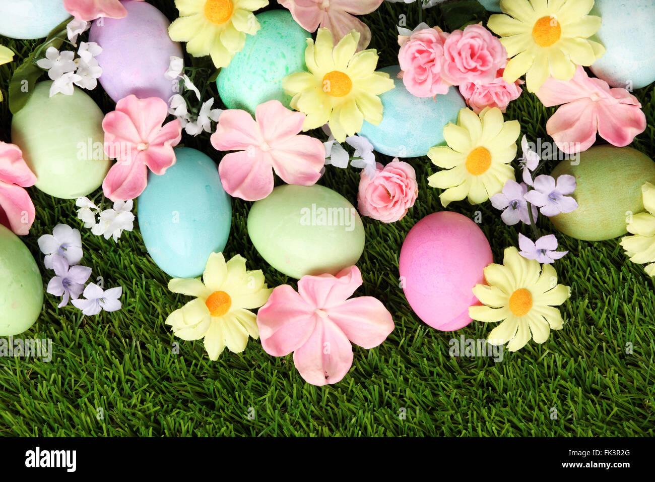Bunte Ostereier auf dem Rasen mit Blumen Hintergrund Stockbild