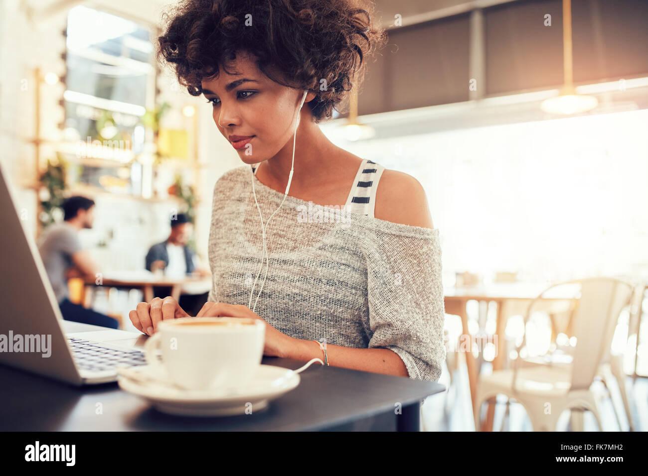 Porträt von einer attraktiven jungen Frau mit Kopfhörern mit Laptop in einem Café. Afrikanische amerikanische Stockbild