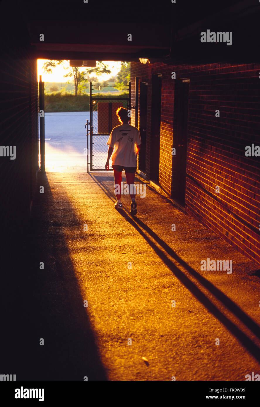 Sonnenuntergang beleuchtet weibliche Läufer verlassen Stadion Spur durch tunnel Stockbild