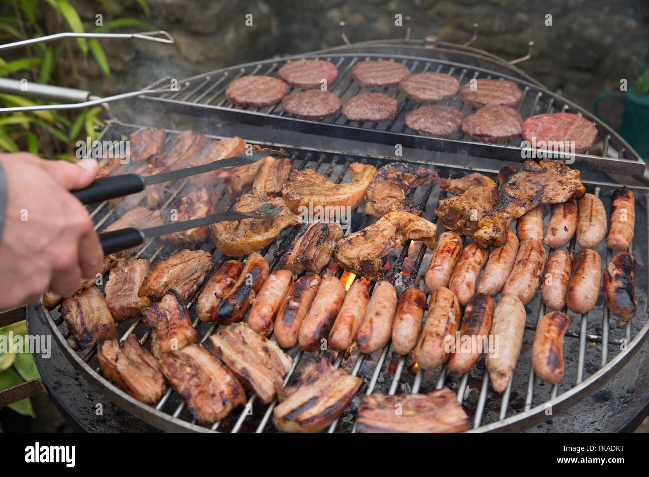 Fleisch grillen auf dem Grill, NotonFest, Milborne Port, Somerset, England, UK Stockbild