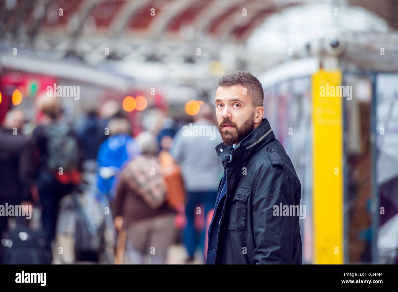 Hipster-Mann wartet am überfüllten Bahnhof Stockbild