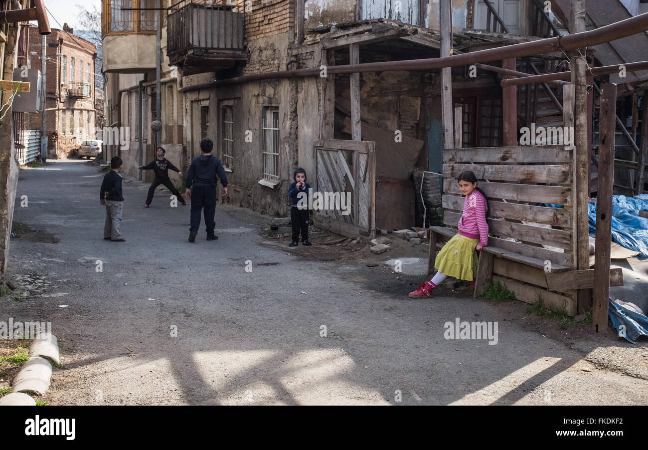 Jungs spielen Straßenfußball das Mädchen in den Vordergrund ist nicht im Spiel enthalten. Tiflis Stockbild