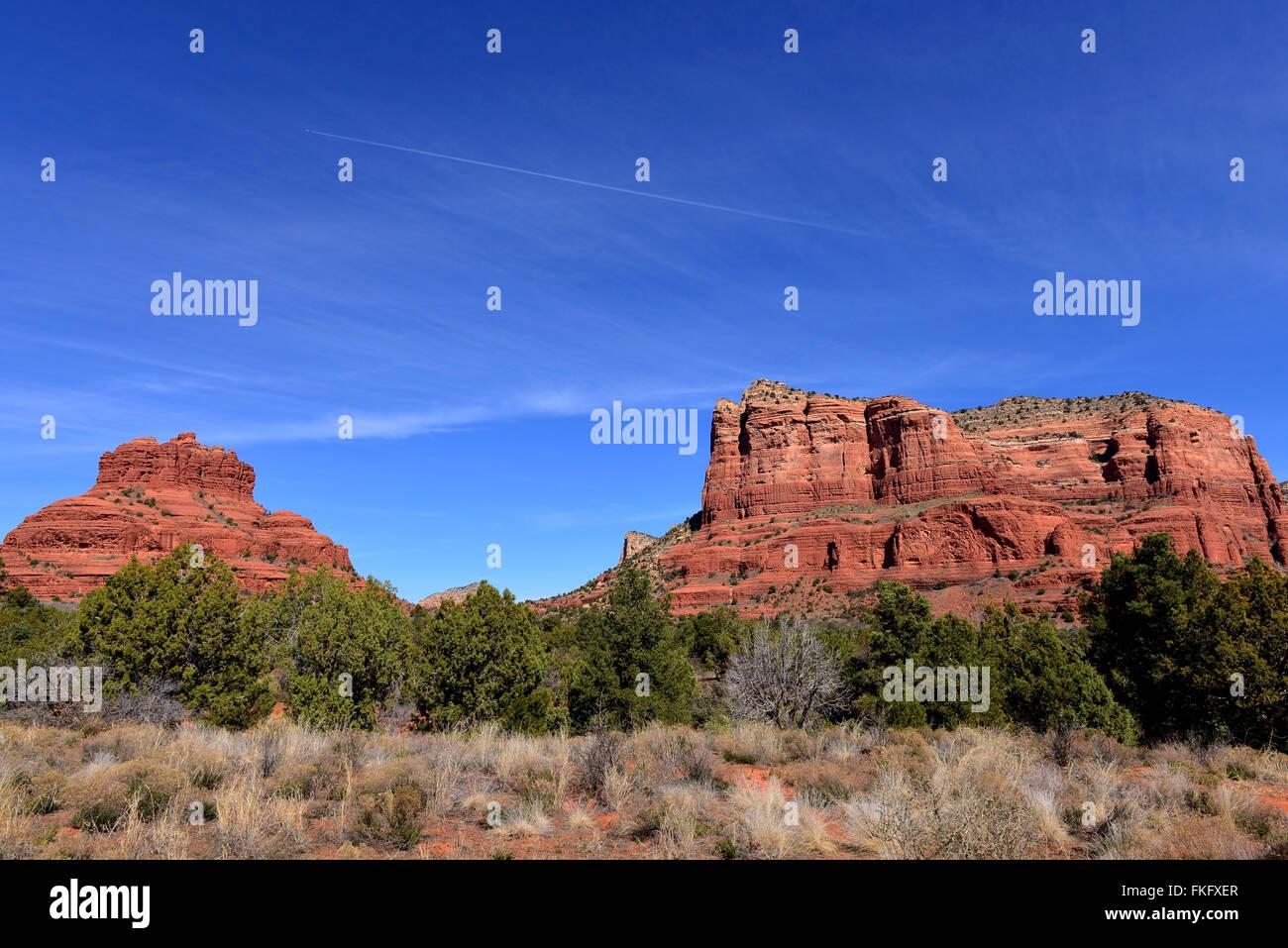 Die roten Felsformationen des Sedona Arizona, mit Bell Rock auf der linken und Jet mit Kondensstreifen am Himmel. Stockbild