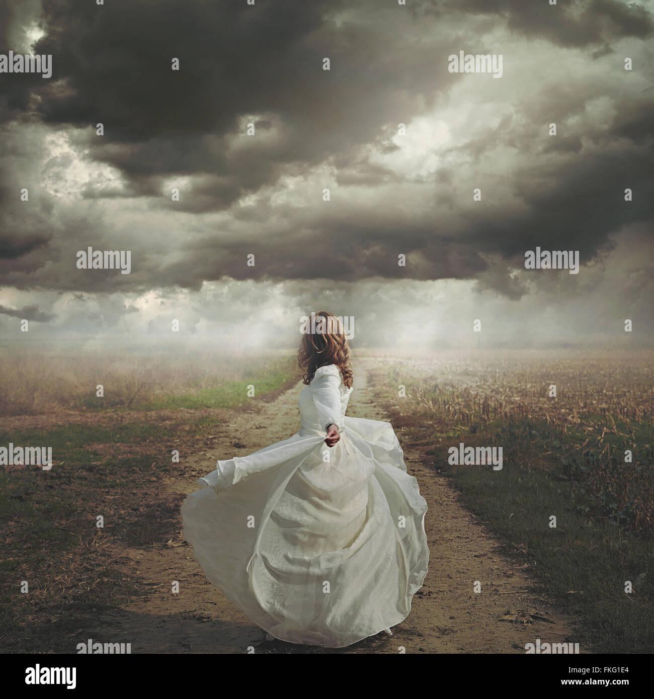 Frau tanzt in desolate Straße. Dramatische und surreale Wolkengebilde Stockbild