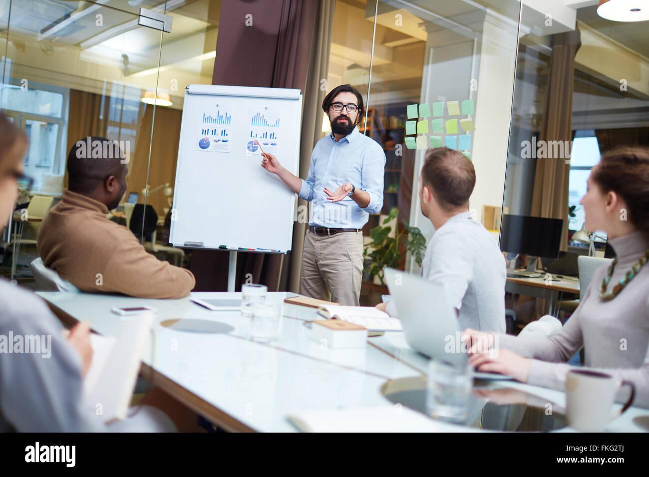 Junge Unternehmer finanzielle Grafiken, seine Partner Tagung zu erklären Stockbild