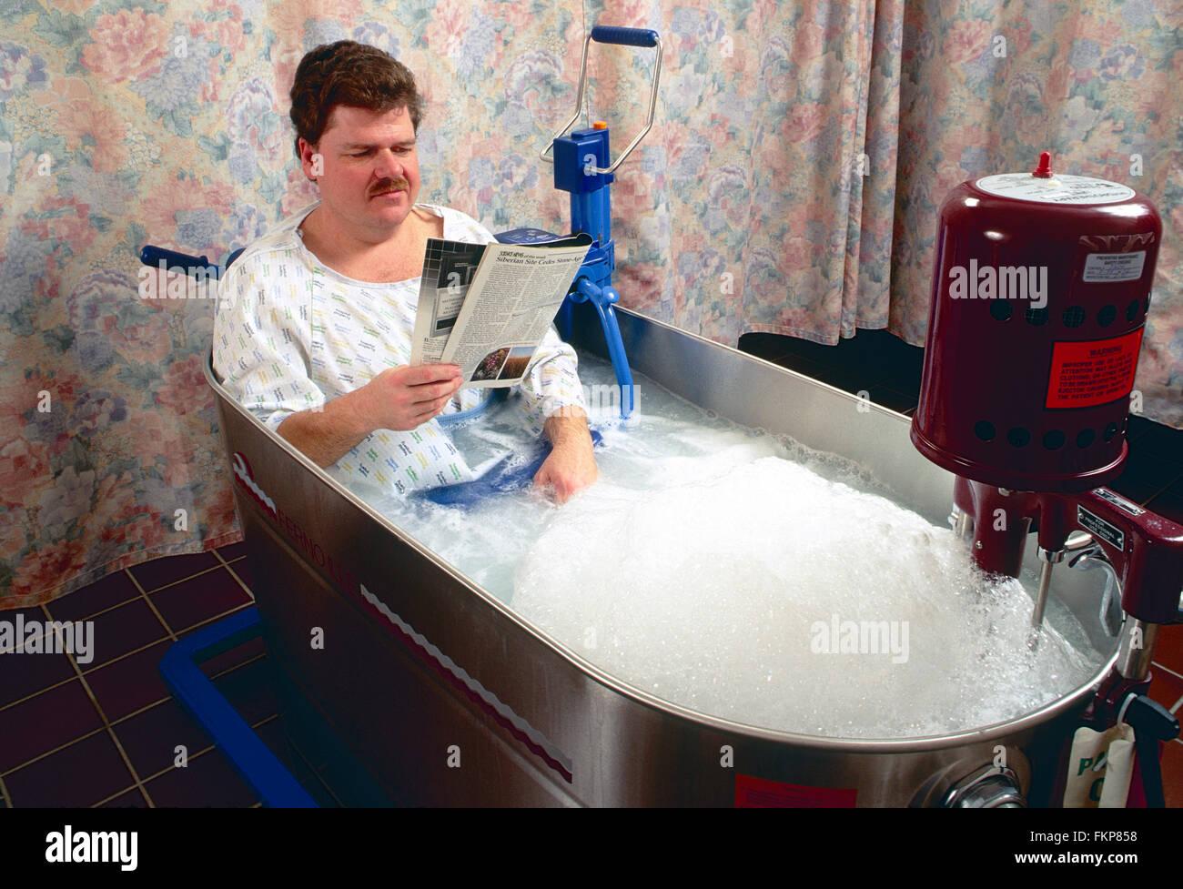 Männliche Patienten im Whirlpool-Badewanne für physikalische Therapie Stockbild